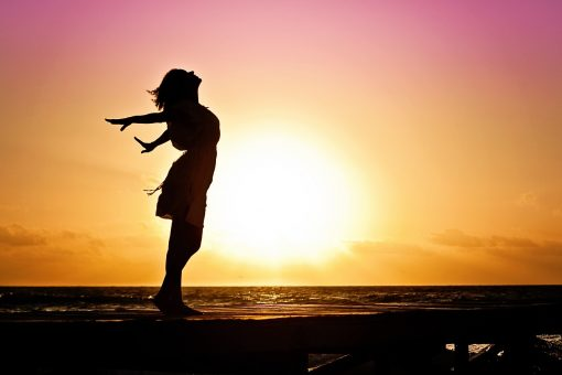 woman standing free with rising sun behind her